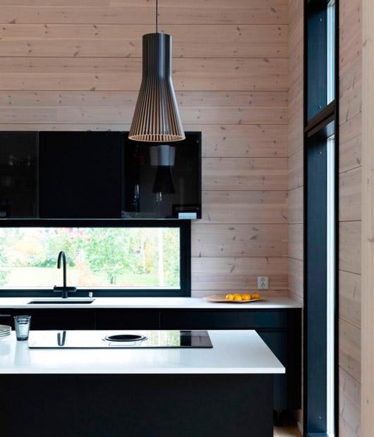 Темная кухня со светлой столешницей в доме из бруса