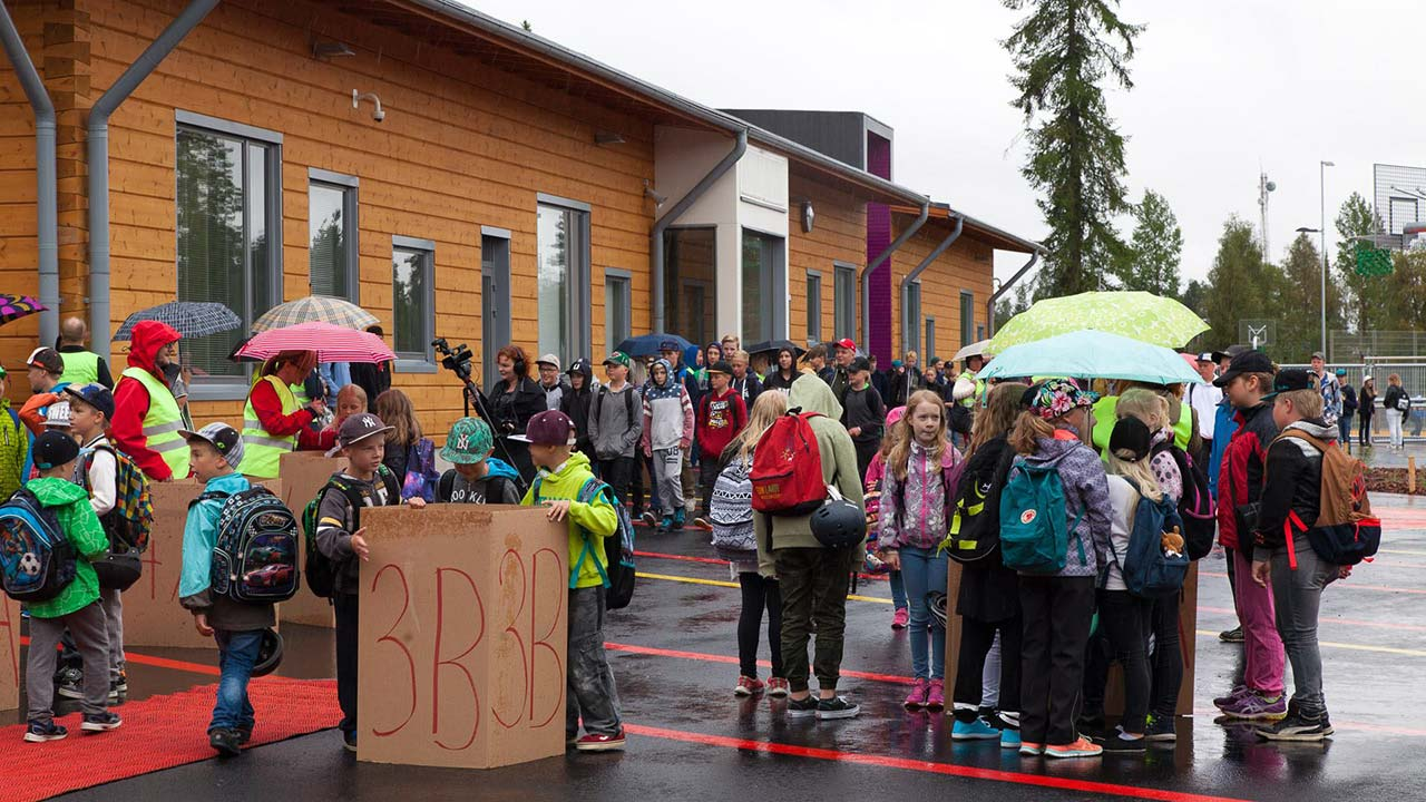 дети собрались возле деревянной школы